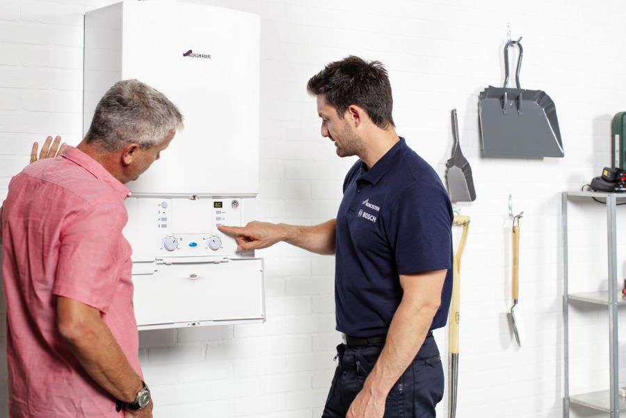 Picture of a Worcester Bosch engineer with a customer and central heating boiler